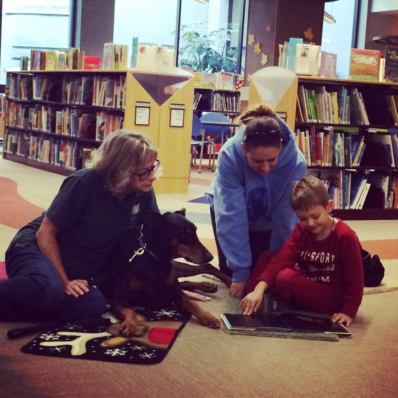 Sioux City resident Dawn Cavenee encourages her son as he reads aloud to an eager Doberman from the K-9 S.T.A.R.S. program.